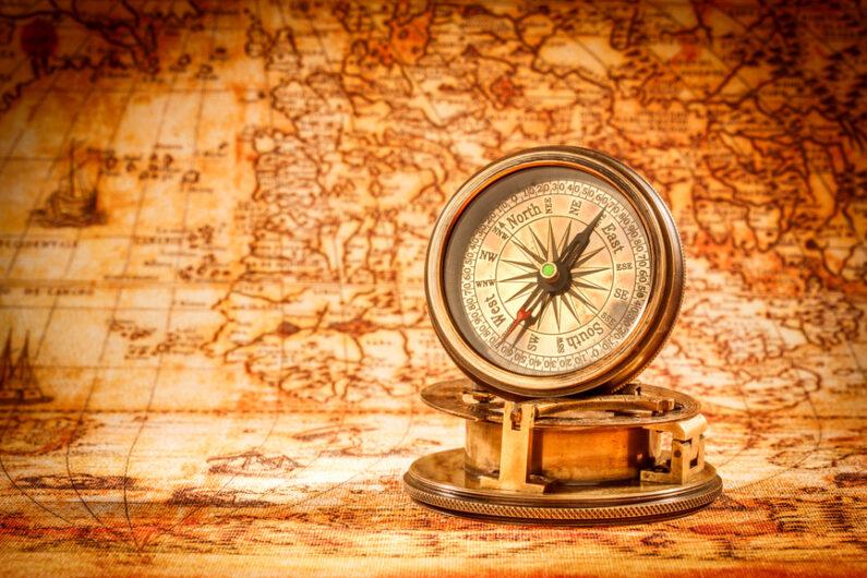 eine alte Weltkarte mit antikem Kompass