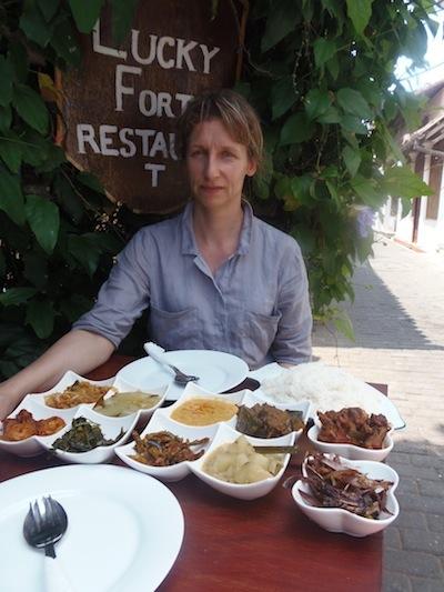 Nadja vor einer Auswahl von zehn verschiedenen Currys im Restaurant
