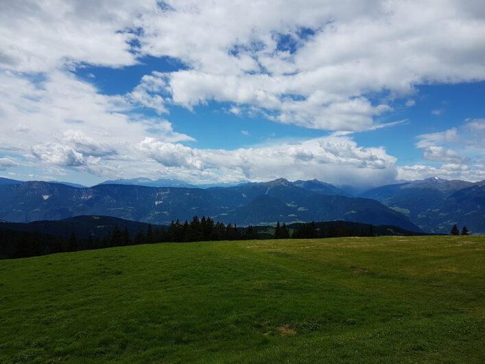 Blick von der Vöraner Alm über die Wiese auf die Südtiroler Berge