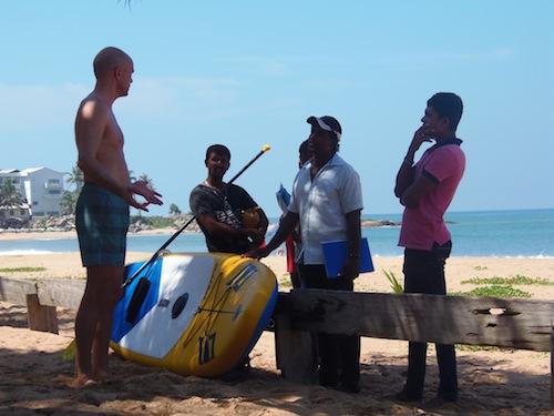 Männer am Strand mit einem Stand-up-Paddelbrett