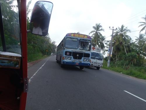 auf einer engen Straße überholt der Bus einen Krankenwagen trotz entgegenkommendem Tuk Tuk