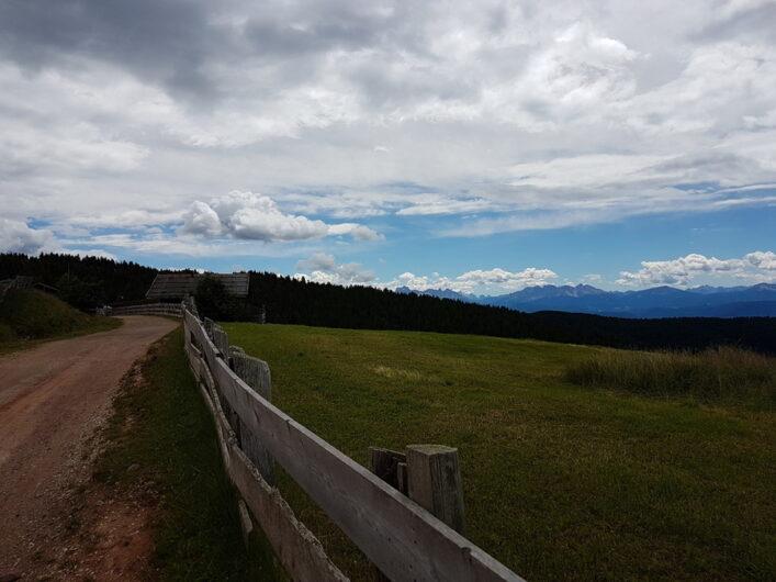 die Vöraner Alm kommt in den Blick und weit in der Ferne die Berggipfel der Dolomiten