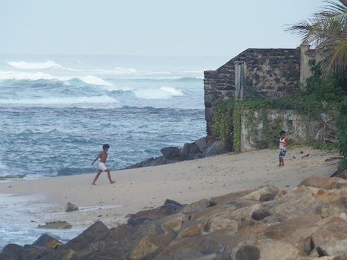 zwei Kinder am Strand bei Mirissa und dahinter tobt das Meer