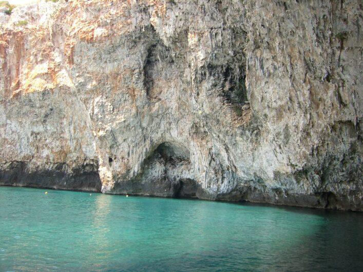 türkis schimmerndes Meer vor der Steilwand an der Grotta Zinzulusa