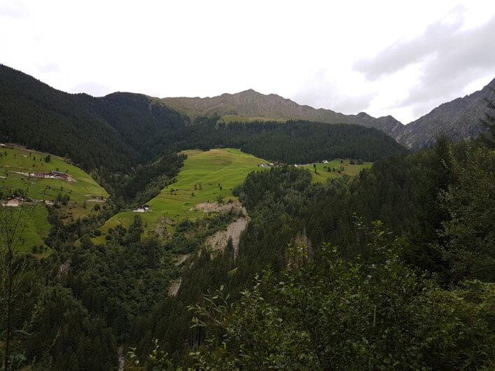 Der Blick geht zurück und hinauf auf den Weiler Videgg, die Videgger Assen und die dahinter liegenden Gipfel.