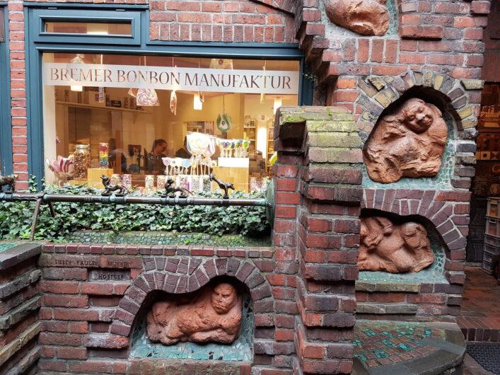 in die Hauswand eingearbeitete Figuren im Handwerkerhof an der Bonbonmanufaktur