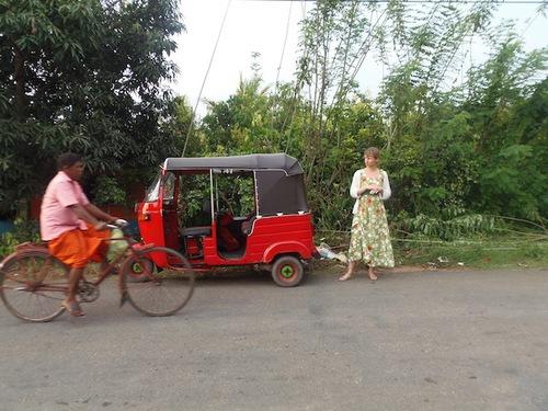 Nadja wartet neben dem roten Tuk Tuk am Straßenrand