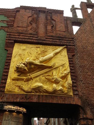 großes goldfarbenes Relief an einer Fassade zu Beginn der Bremer Böttcherstraße
