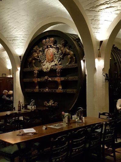 stilvolle Atmosphäre vor einem reich verzierten Holzweinfass im Gewölbe des Bremer Ratskellers