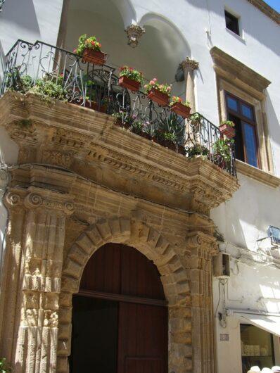 pittoresker Balkon mit Blumen über einem steinernen Eingangsportal in Gallipoli
