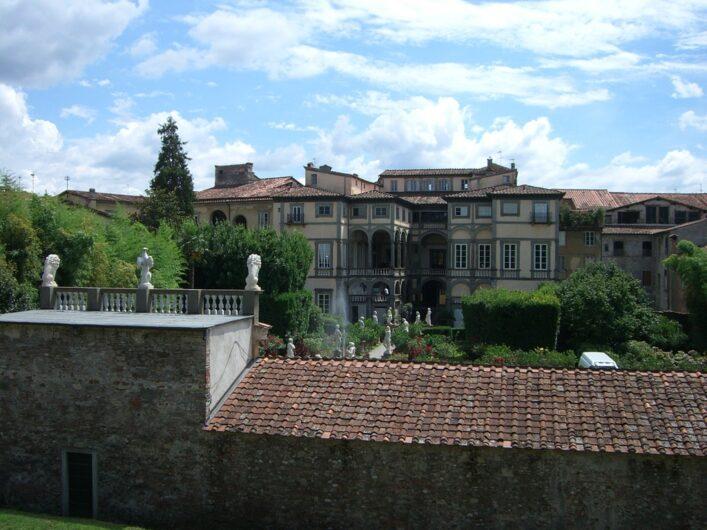auf dem Stadtwall in Lucca mit Blick auf herrlich bepflanzte Innenhöfe mit Skulpturen