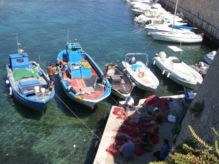am Hafen von Gallipoli reparieren Fischer vor ihren Booten die Netze