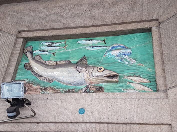 Fresko mit Fisch oberhalb einer Eingangstür zu einem fischverarbeitenden Betrieb