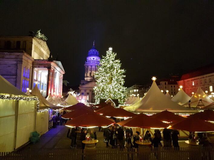Blick von oben auf den Weihnachtszauber am Gendarmenmarkt mit den weißen Zelten, dem Weihnachtsbaum und dem Französischen Dom im Hintergrund