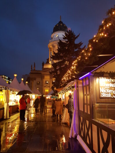 zwischen den Buden auf dem Weihnachtsmarkt am Gendarmenmarkt mit Blick auf den Deutschen Dom