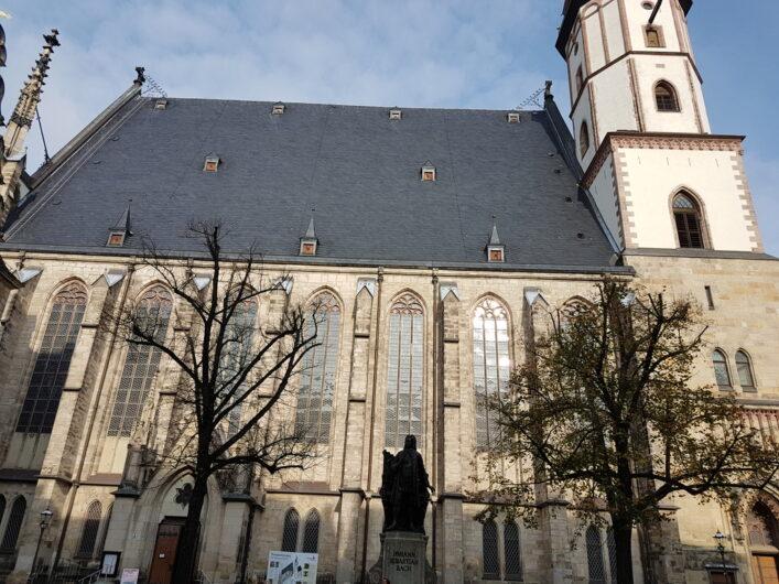 ein seitlicher Blick auf die Thomaskirche mit der Statue von Johann Sebastian Bach davor