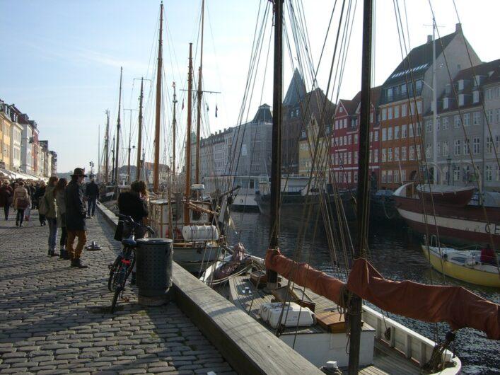 Blick auf die bunten Häuser und Segelschiffe im Hafenarm von Nyhavn