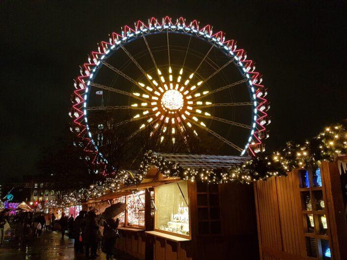 Buden auf dem Weihnachtsmarkt am Roten Rathaus und Blick auf das Riesenrad dahinter