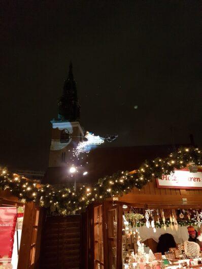 der Weihnachtsmann schwebt auf seinem Schlitten über die Buden am Roten Rathaus