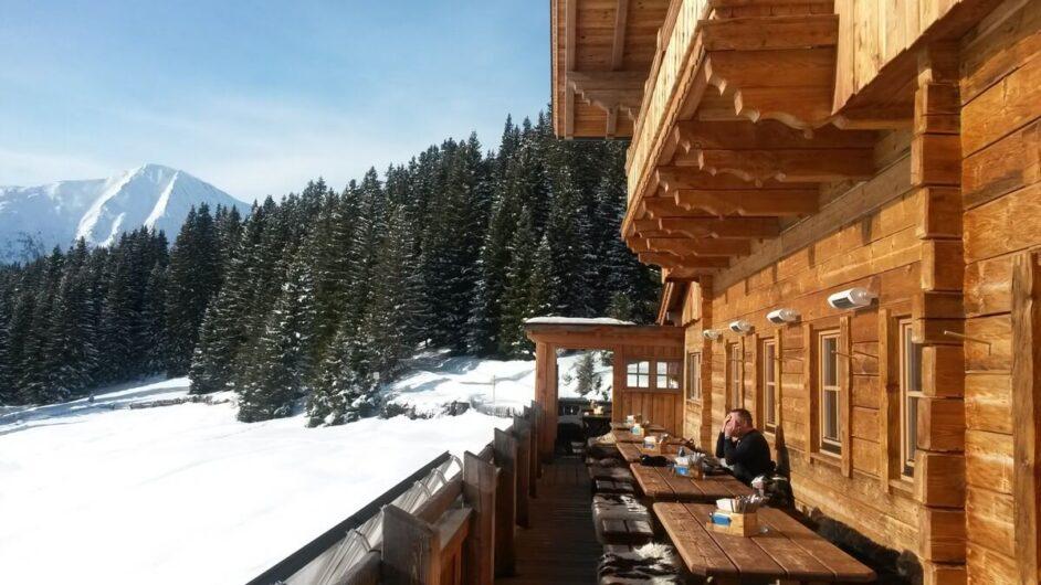 die Sonne und die herrlich verschneite Bergwelt auf der Terrasse der Hög Alm in Serfaus genießen