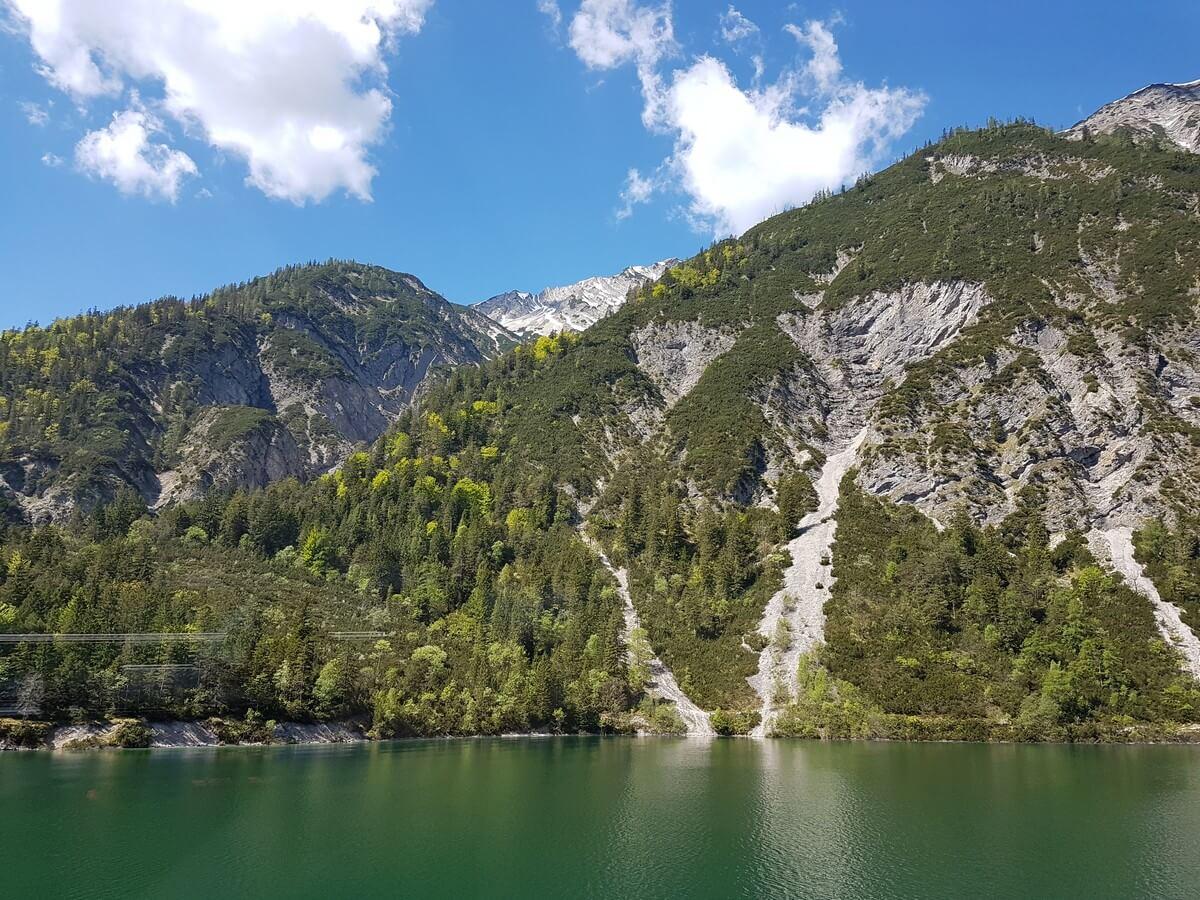 bewaldete Felsen reichen hinunter an das Ufer des dunkelgrün schimmernden Achensees