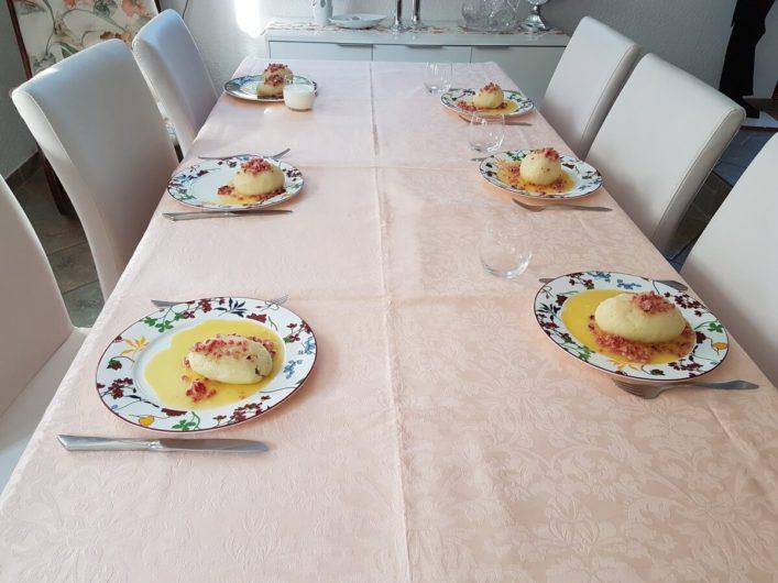 die Teller mit den fertigen Berheè stehen auf dem gedeckten Tisch