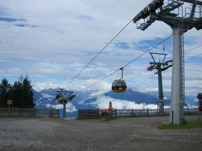 die Kabinen der Umlaufbahn Falzeben an der Bergstation mit Ausblick auf die gegenüberliegenden Berggipfel der Ortlergruppe
