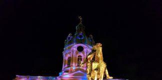 Blick auf das erleuchtete Schloss Charlottenburg und die Dächer der Weihnachtsmarktbuden