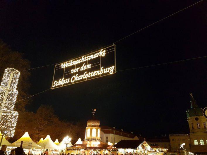 Eingang zum Weihnachtsmarkt am Schloss Charlottenburg mit den erleuchteten Ständen und dem Schloss Charlottenburg