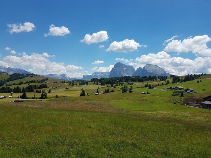Blick über die saftigen Wiesen der Seiser Alm bis hin zu den Gipfeln der Dolomiten
