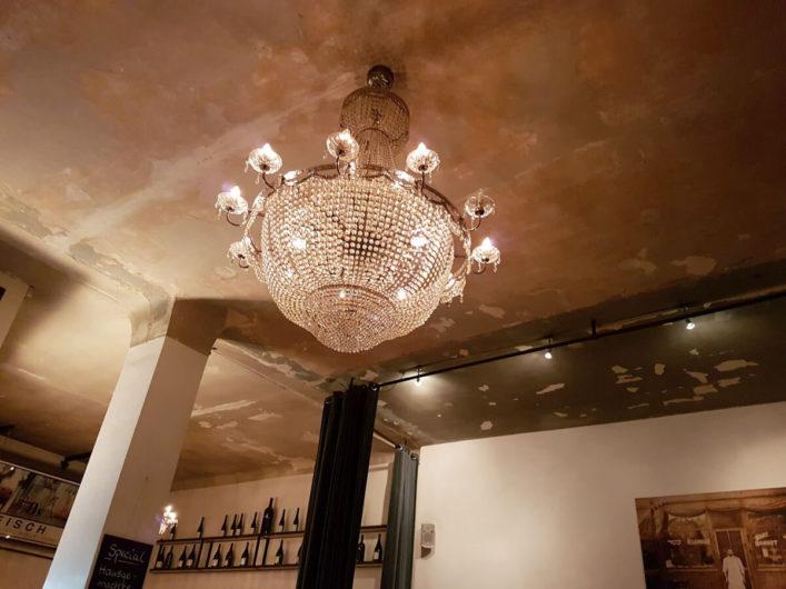 Interior des Restaurants Fleischerei in Berlin mit großem Leuchter und Foto an der Wand