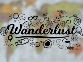der Text Wanderlust ist umgeben von vielen Reiseutensilien