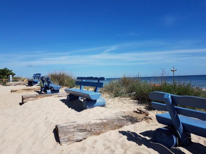 blaue Bänke im Sand und dahinter Blick auf die Ostsee