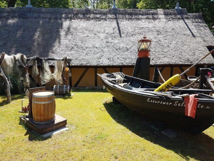 Salzhütten in Koserow mit altem Holzfass und Fischerkahn davor