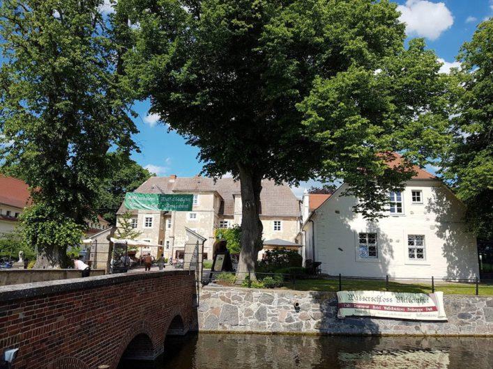 Blick auf das Wasserschloss Mellenthin und die Brücke über den Wassergraben