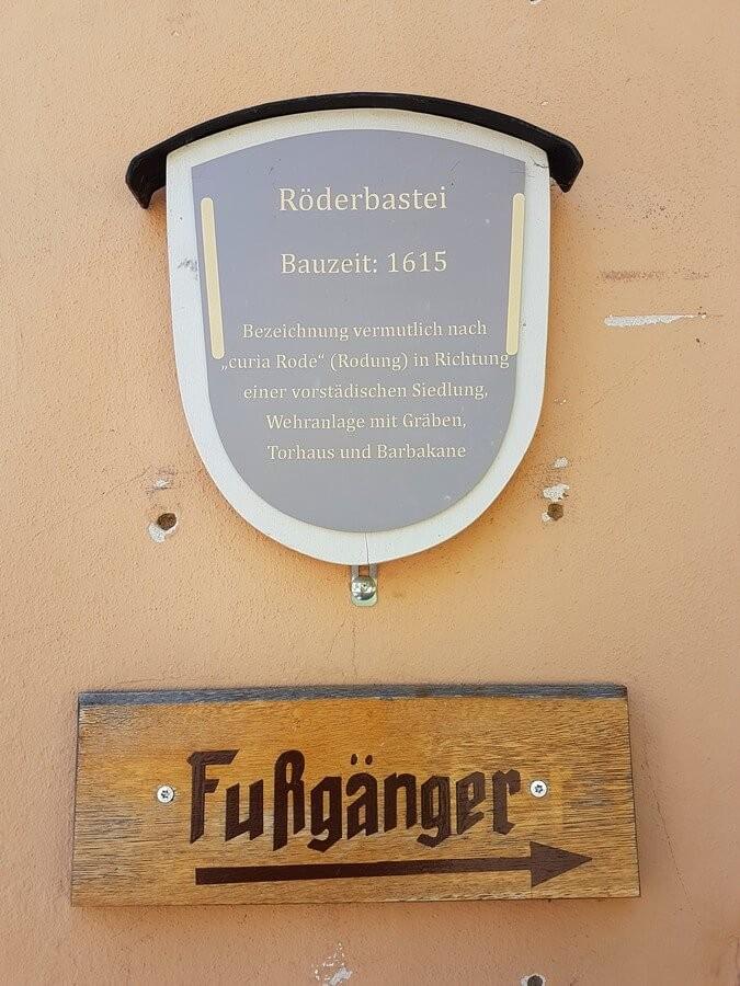 Schild mit Erklärungen zum Rödertor in Rothenburg und Fußgängerhinweis