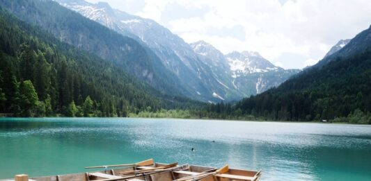 2 Holzboote auf dem grün-blau schimmernden Jägersee vor einer Bergkulisse