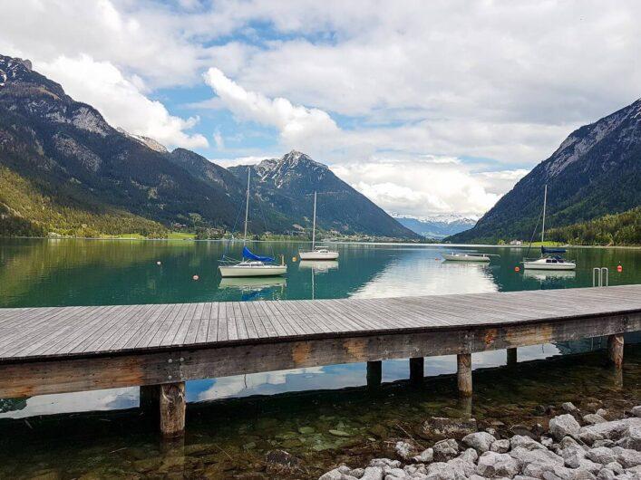 Blick auf den Achensee mit Segelbooten und den Bergen im Hintergrund