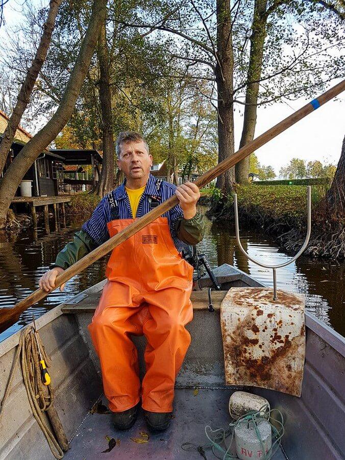 Fischer Laszlo rudert über das Fließ Richtung See