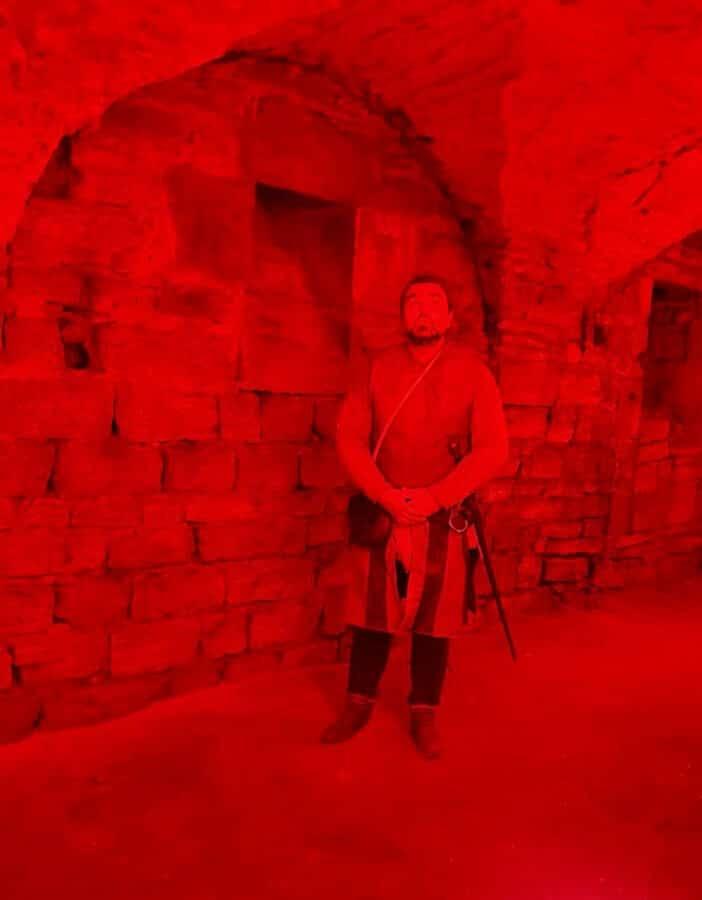 Schwertkämpfer im rot erleuchteten Gewölbe des Petriklosters