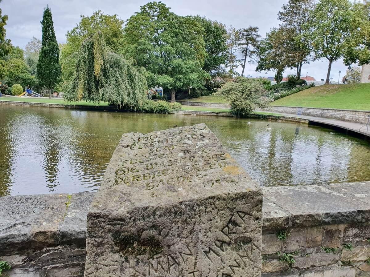 Stein mit Aufschrift vor einem Paderquellbecken