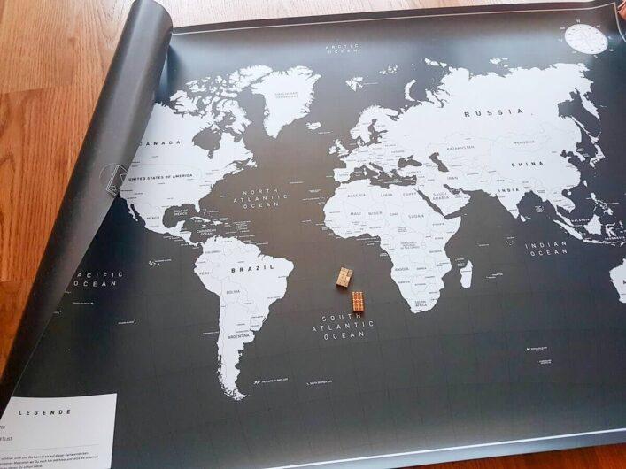 die noch halb aufgerollte magnetische Weltkarte mit den mitgelieferten Magneten