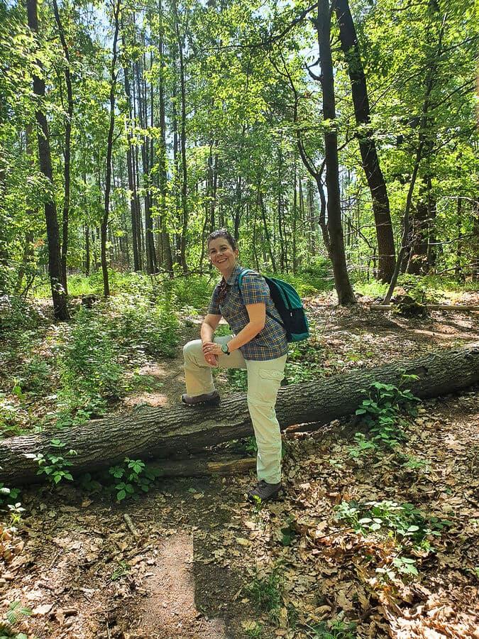 Martina an einem Baumstamm, der auf dem Weg liegt