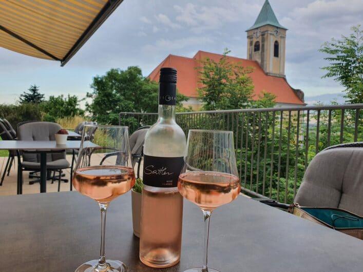 Roséwein in Gläsern und die Dorfkirche von Jois