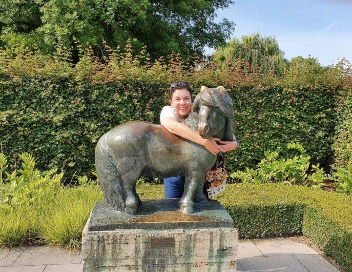 Martina umarmt Pferdeskulptur auf der Bundesgartenschau