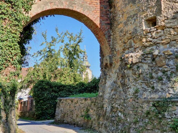 Blick durch die Stadtmauer Richtung Altstadt Hartberg und Kirche St. Martin