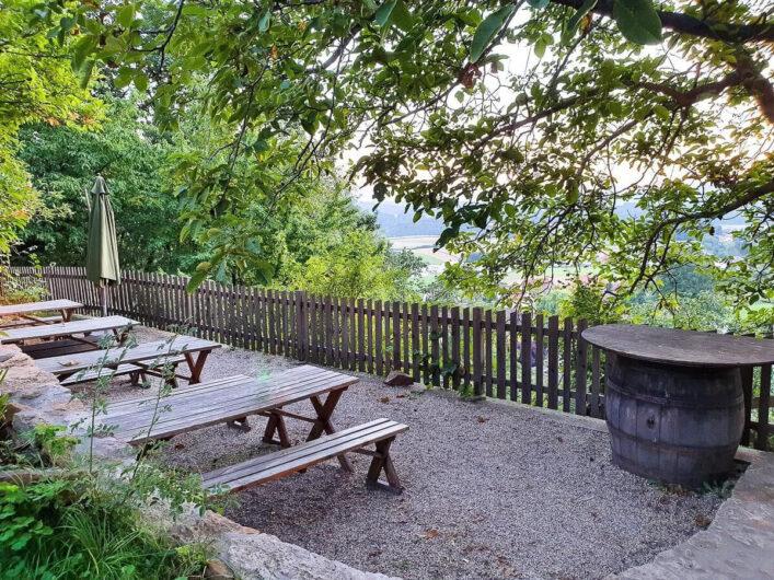 Gastgarten vom Buschenschank Schmallegger mit Biertischen und Bänken und umgeben von Bäumen