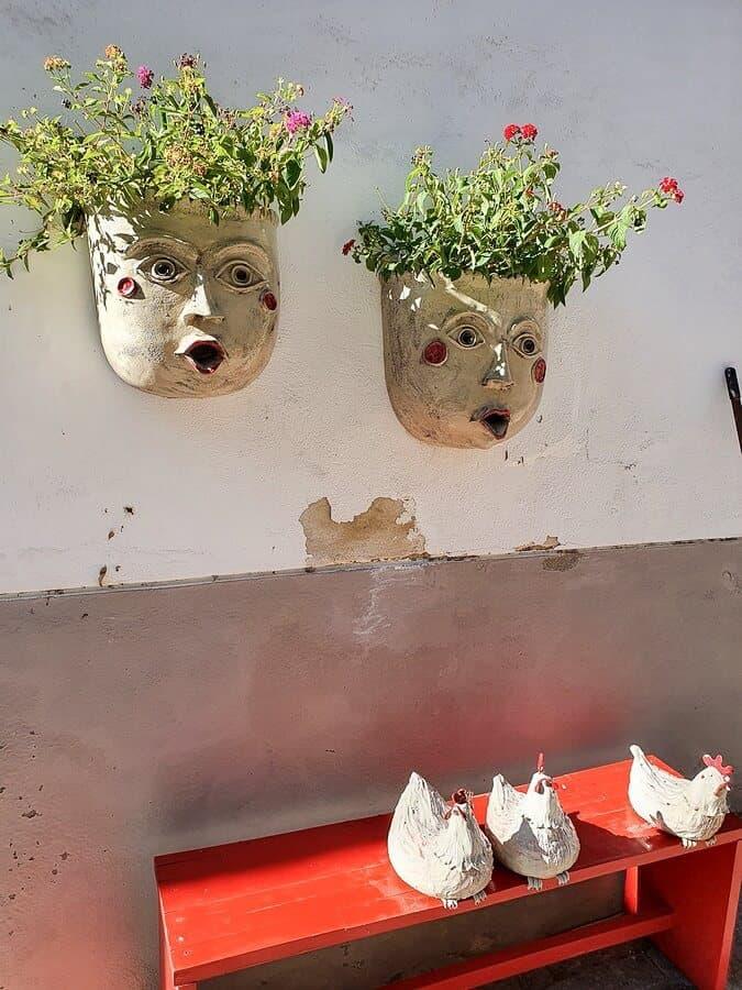 bepflanzte Keramikgesichter und Keramikhühner als Dekoration