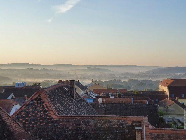 Blick über die morgendlichen Dächer von Hartberg in der Steiermark auf die Hügel der Region.
